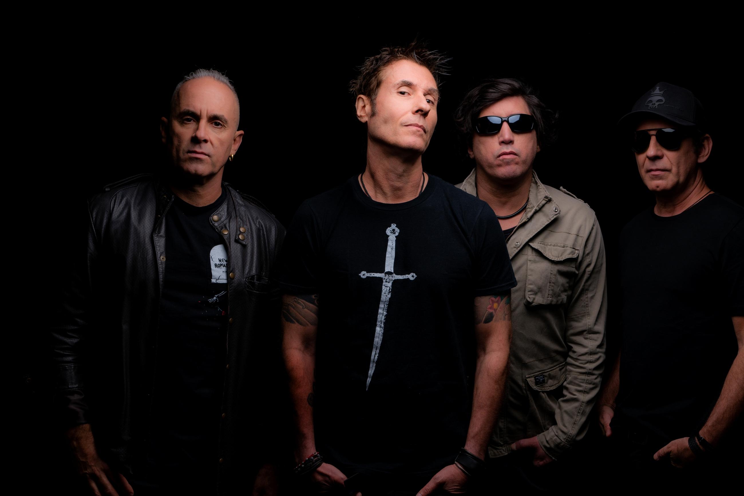 Integrantes da banda Capital Inicial em pose de divulgação para a nova turnê em um ambiente escuro com destaque para a face de cada músico.