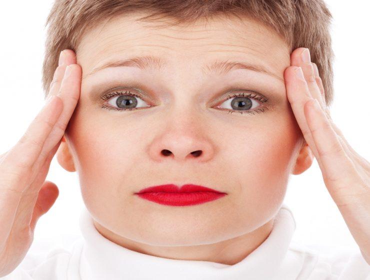 Mulher com as mãos na cabeça indicando que sofre com dores de cabeça